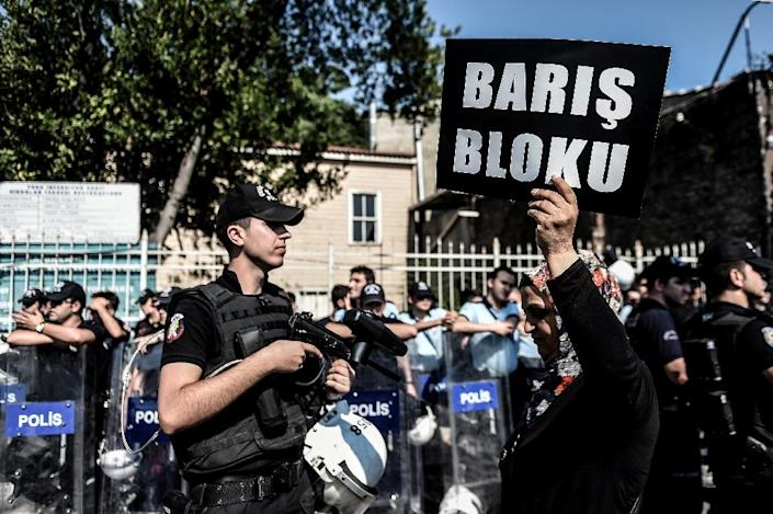"""A Turkish activist holds a sign reading """"Peace block"""" after authorities banned a rally in the Aksaray district of Istanbul, on July 26, 2015 (AFP Photo/Ozan Kose)"""