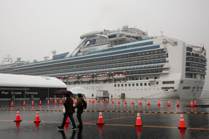 Visitors walk past the quarantined Diamond Princess cruise ship in Yokohama, near Tokyo. Americans who have not testes positive for the virus will be flown back home on chartered flights Sunday, but will face another two-week quarantine. (ASSOCIATED PRESS)