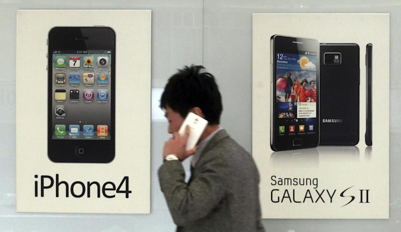 FILE - In this Nov. 22, 2013 file photo, a man walks past banners advertising smartphones by Samsung and Apple at a mobile phone shop in Seoul, South Korea. The high-stakes battle between the world's largest smartphone makers is scheduled to wrap up this week after a monthlong trial that has pulled the curtain back on just how very cutthroat the competition is between Apple and Samsung. Closing arguments in the patent-infringement case are scheduled to begin Monday, April 28, 2014 with the two tech giants accusing each other, once again, of ripping off designs and features. At stake: $2 billion if Samsung loses, a few hundred million if Apple loses. (AP Photo/Yonhap, Han Sang-kyun, File) KOREA OUT