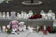 Flowers and candles were left after a man killed several people, in Kongsberg, Norway, Thursday, Oct. 14, 2021. Police in Norway are holding a 37-year-old man from Denmark suspected in a bow-and-arrow attack in a small town that killed five people and wounded two others. (Terje Pedersen/NTB via AP)