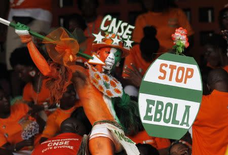 A fan of Ivory coast holds a sign with a message against Ebola during the 2015 African Nations Cup qualifying soccer match between Ivory Coast and Sierra Leone in Abidjan
