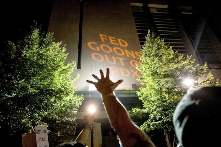 "Protesters raise their arms as text reading ""Fed goons out of PDX"" is projected onto the courthouse in Portland"