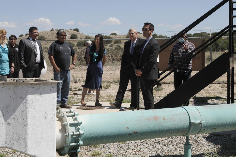 Congresswoman Teresa Leger Fernández, center left, and Agriculture Secretary Tom Vilsack, center, visit a wastewater treatment plant on Wednesday, July 7, 2021, in Ohkay Owingeh, New Mexico. (AP Photo/Cedar Attanasio)