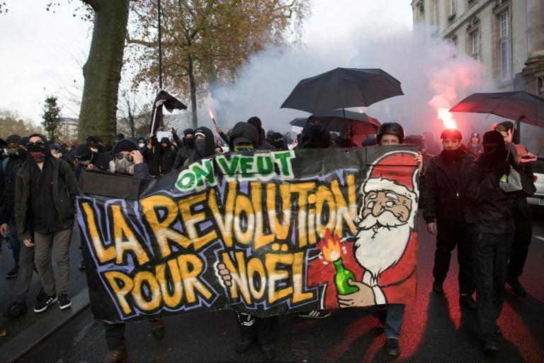 "Manifestantes marchan contra la reforma de las pensiones y la precariedad con una pancarta en la que se puede leer ""Queremos la revolución para Navidad"" en Nantes, Francia, el 7 de diciembre de 2019 Protesters march with a banner reading 'we want the revolution for Christmas' during a demonstration against unemployment and precariousness in Nantes, western France, on December 7, 2019.The most serious nationwide strike to hit France in years caused new misery for weekend travellers on December 7, with defiant unions dismissing proposals by the government and warning walkouts would last well into next week"