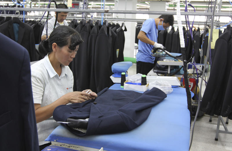 In this photo taken on Sept. 21, 2012 photo, a North Korean woman sews a button on a suit at a factory in Kaesong, North Korea, run by ShinWon, a South Korean clothing maker. Since April 3, North Korean authorities have barred South Koreans, including ShinWon managers, from entering North Korea through the Demilitarized Zone to get to the Kaesong industrial complex where some 120 South Korean companies run factories employing North Korean workers. (AP Photo/Jean H. Lee)