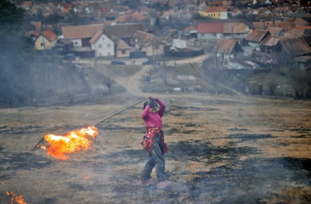 In this photo taken on Sunday, March 10, 2019, a little girl spins a burning tire on a metal chain during a ritual marking the upcoming Clean Monday, the beginning of the Great Lent, 40 days ahead of Orthodox Easter, on the hills surrounding the village of Poplaca, in central Romania's Transylvania region. Romanian villagers burn piles of used tires then spin them in the Transylvanian hills in a ritual they believe will ward off evil spirits as they begin a period of 40 days of abstention, when Orthodox Christians cut out meat, fish, eggs, and dairy. (AP Photo/Vadim Ghirda)