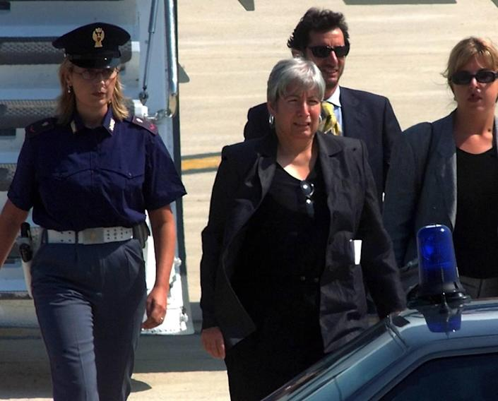 FILE- An August 25, 1999 file photo showing police escorting Italian convict Silvia Baraldini, center, who was assigned to house arrest due to health reasons, Rome, Saturday, April 21, 2001. Baraldini was convicted in the United States for armed robberies that financed leftist terrorist organization and has been in Italy since 1999 to cure a breast cancer. (AP Photo/Massimo Sambucetti/files)