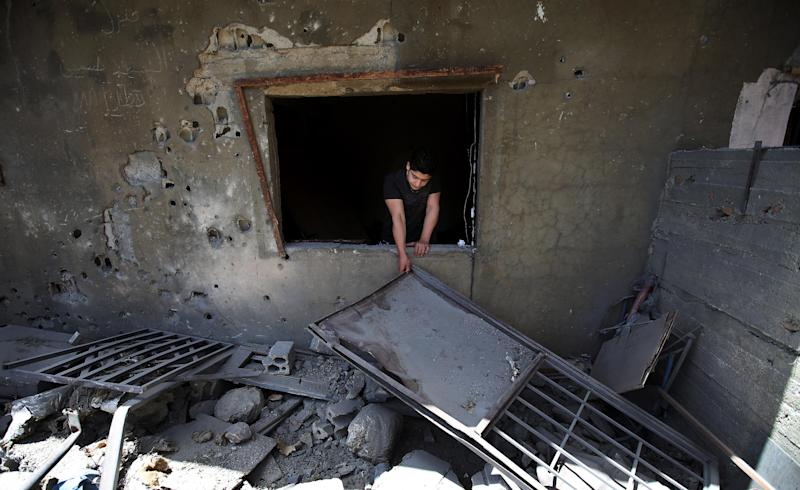 A Lebanese man removes debris from his damaged house, hit by rockets fired by Syrian rebels according to villagers, in Hermel town, northeast of Lebanon, Wednesday May 29, 2013. Shells fire from Syria regularly strike the Lebanese northeastern town of Hermel, a predominantly Shiite town. Sectarian tensions in Lebanon have been on the rise, particularly as a result of the involvement of the militant Hezbollah group in fighting in Syria alongside President Bashar Assad's forces. (AP Photo/Hussein Malla)
