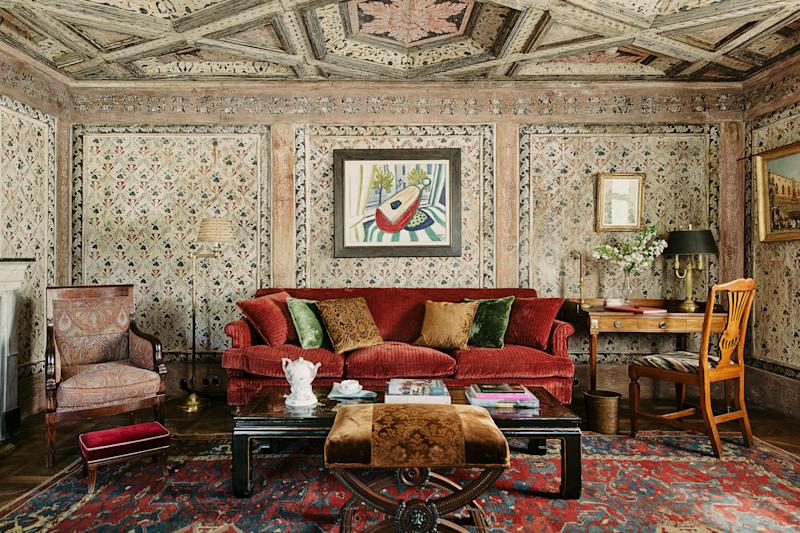 The living room walls and ceiling are covered with wooden Tyrolean paneling from the 18th century. Werner Heldt painting; custom sofa by Studio Peregalli in a red silk velvet; antique Chinese low table.