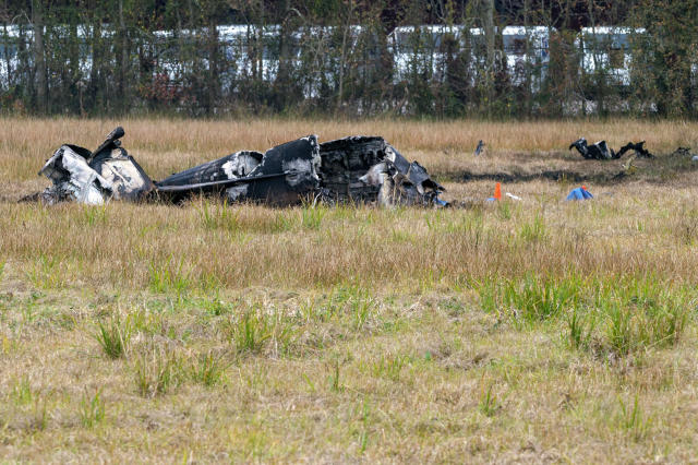 A view of the burnt wreckage of a small plane that crashed into the parking lot of a post office is shown, at left, in Lafayette, La., Saturday, Dec. 28, 2019. Several people died in the crash. (Scott Clause/The Lafayette Advertiser via AP)