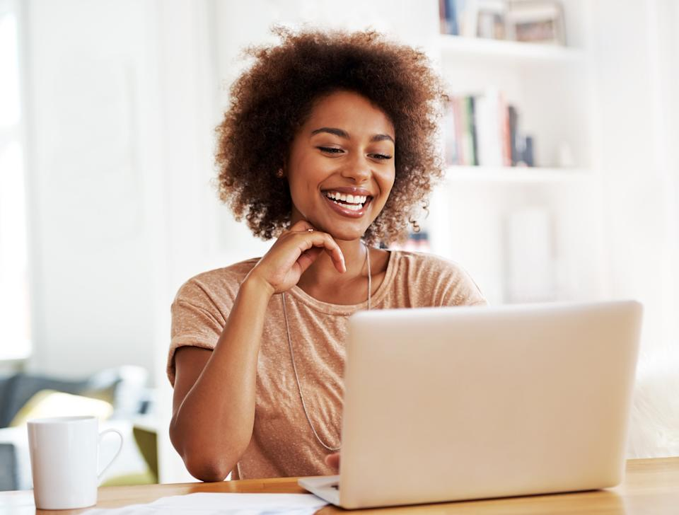 A laughing ethnic woman looking at her laptop