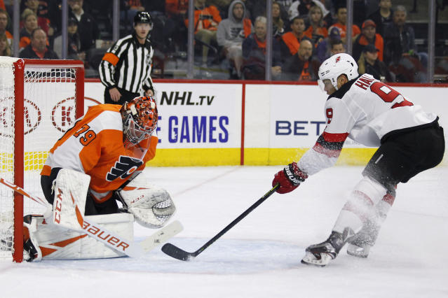 Philadelphia Flyers' Carter Hart, left, stops a shot by New Jersey Devils' Taylor Hall during the first period of an NHL hockey game Wednesday, Oct. 9, 2019, in Philadelphia. (AP Photo/Tom Mihalek)