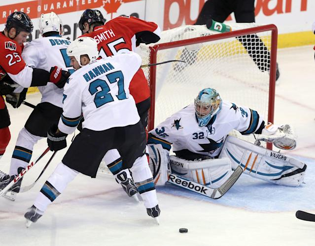 San Jose Sharks goaltender Alex Stalock (32) keeps his eyes on a loose puck as teammates Scott Hannan (27) and Jason Demers (5) defend against Ottawa Senators' Chris Neil (25) and Zack Smith (15) during first period NHL hockey game in Ottawa, Ontario, on Sunday, Oct. 27, 2013. (AP Photo/The Canadian Press, Fred Chartrand)