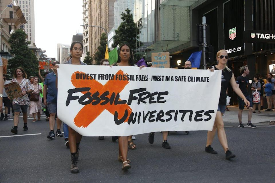 Three protesters carry a sign that reads 'Fossil Free Universities'