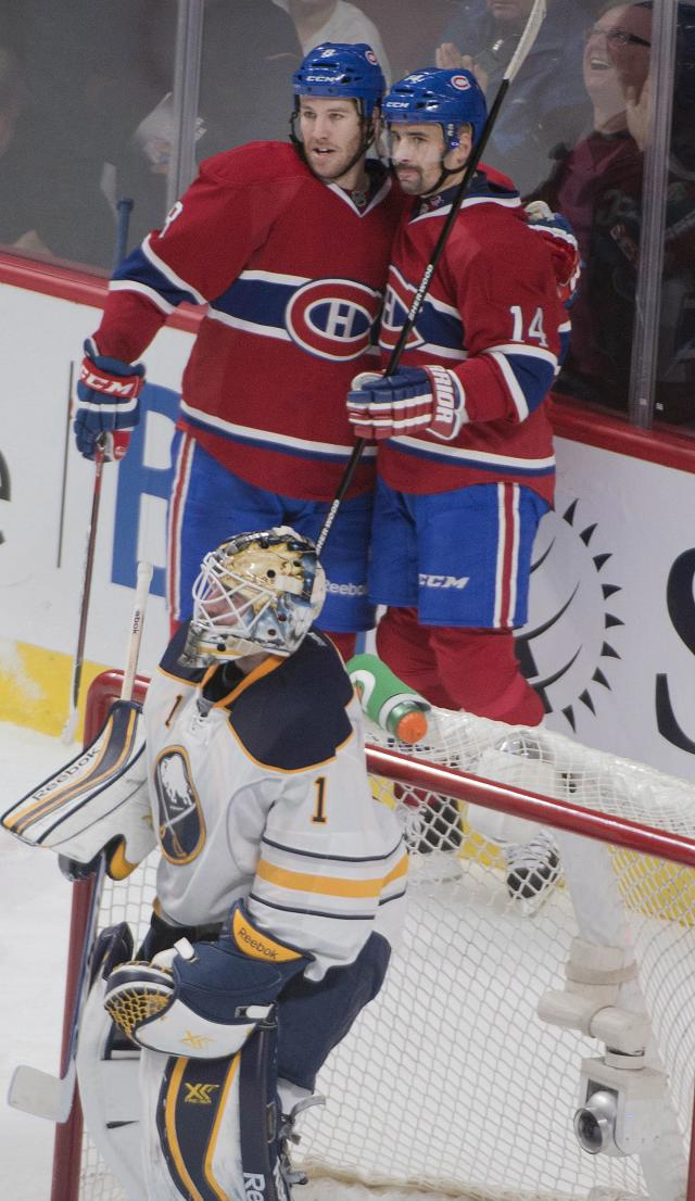 Montreal Canadiens center Tomas Plekanec (14) and right wing Brandon Prust (8) celebrate a goal by Plekanec against Buffalo Sabres goalie Jhonas Enroth (1) during second period NHL action in Montreal, Saturday, Dec.7, 2013. (AP Photo/The Canadian Press, Peter McCabe)