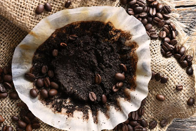 An image of a used coffee filter with coffee beans and burlap cloth on an old wooden table.