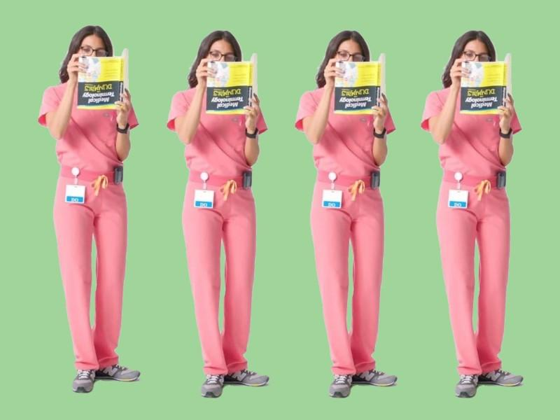 "A female doctor holding a ""Dummies"" book upside down was used by the company Figs to promote scrubs. (Photo: Figs)"