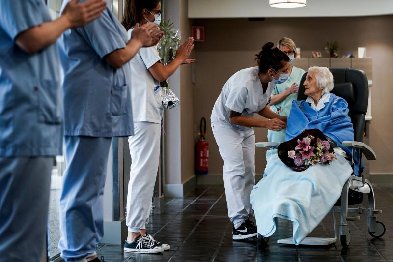 Medical workers clap as Belgian 100 year-old patient Julia Dewilde leaves the Bois de l'Abbaye hospital (CHBA) in Seraing, after being succesfully treated for COVID-19, the disease caused by the novel coronavirus, on April 29, 2020. (Photo by Kenzo TRIBOUILLARD / AFP) (Photo by KENZO TRIBOUILLARD/AFP via Getty Images)