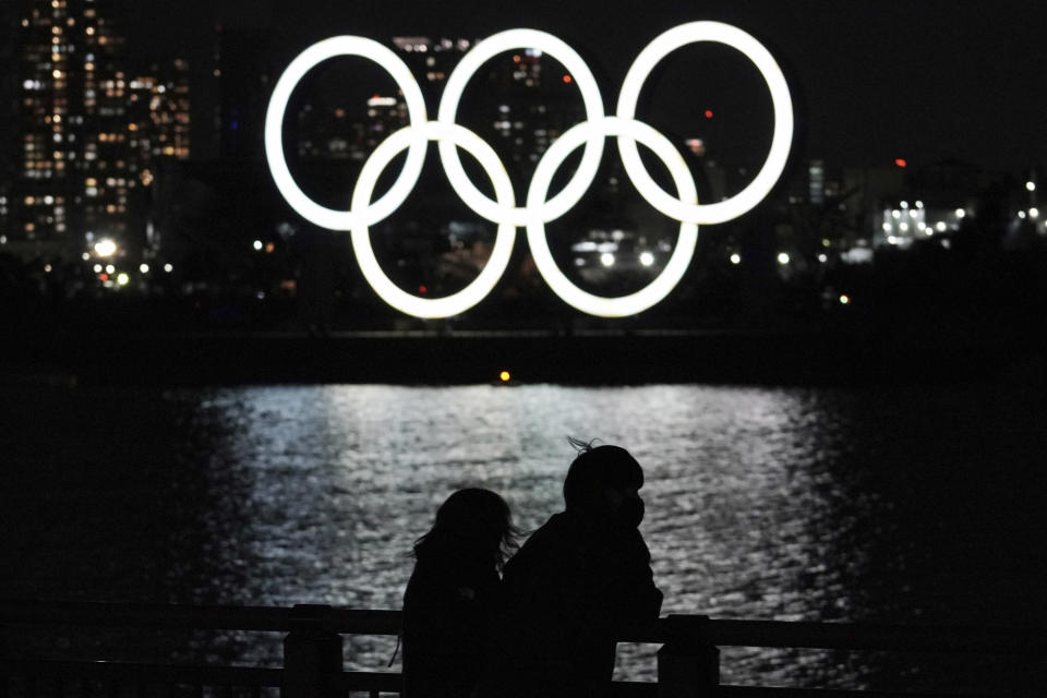 FILE - In this March 3, 2021, file photo, a man and a woman look at the Olympic rings installed off the Odaiba Marine Park in Tokyo. Japan's top telecommunications company is getting 7.3 billion yen, about $67 million, in taxpayer money to design mobile tracking software to curb the spread of coronavirus infections during the Tokyo Olympics. (AP Photo/Eugene Hoshiko)