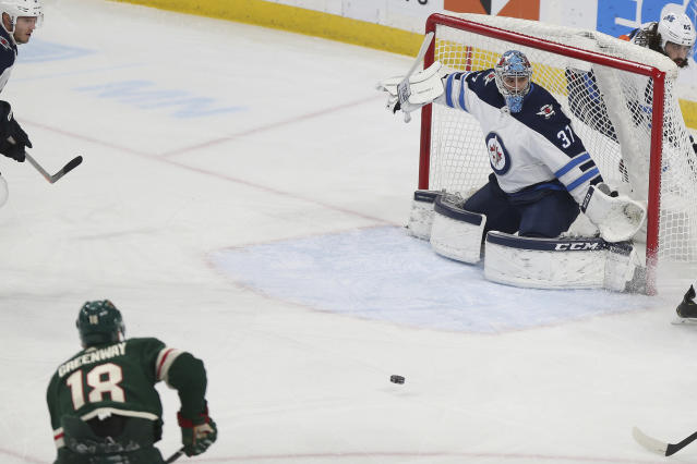 Minnesota Wild's Jordan Greenway (18) shoots a goal against Winnipeg Jets' goalie Connor Hellebuyck (37) in the first period of an NHL hockey game Thursday, Jan. 10, 2019, in St. Paul, Minn. (AP Photo/Stacy Bengs)
