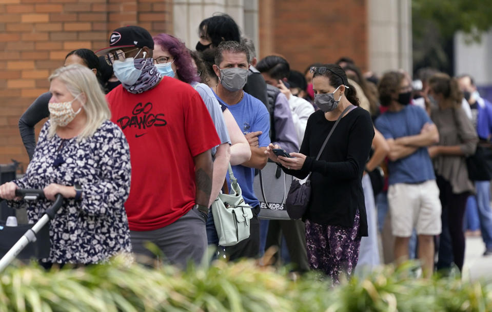 Voters line up and wit to cast a ballot at the American Airlines Center during early voting Thursday, Oct. 15, 2020, in Dallas. (AP Photo/LM Otero)