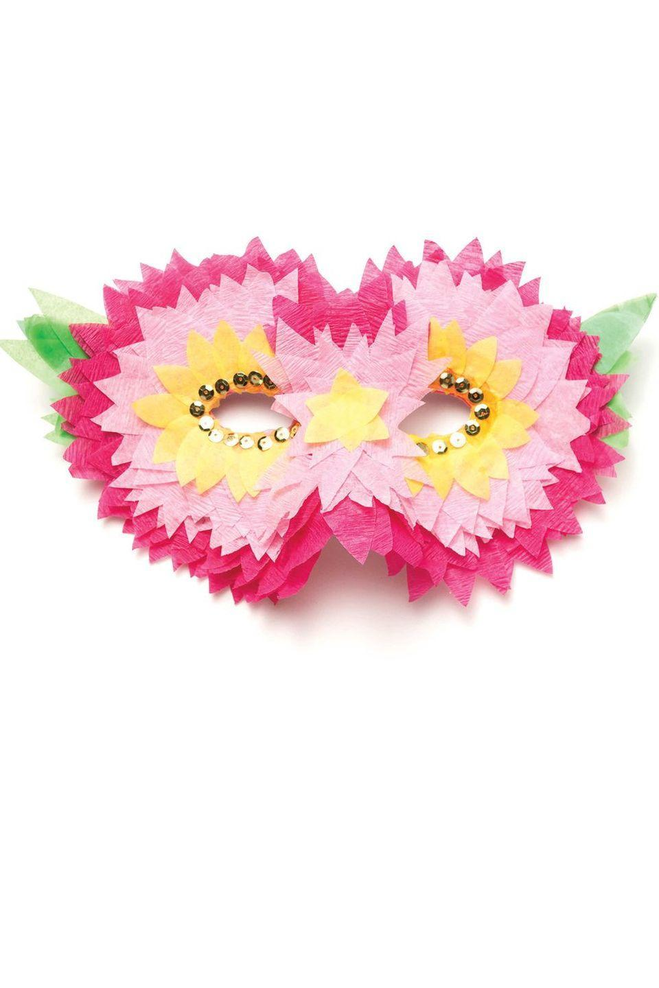 <p>Pink, green, and yellow crepe paper layers — as well as some gold sequins — make for a simply stunning flower mask. </p>