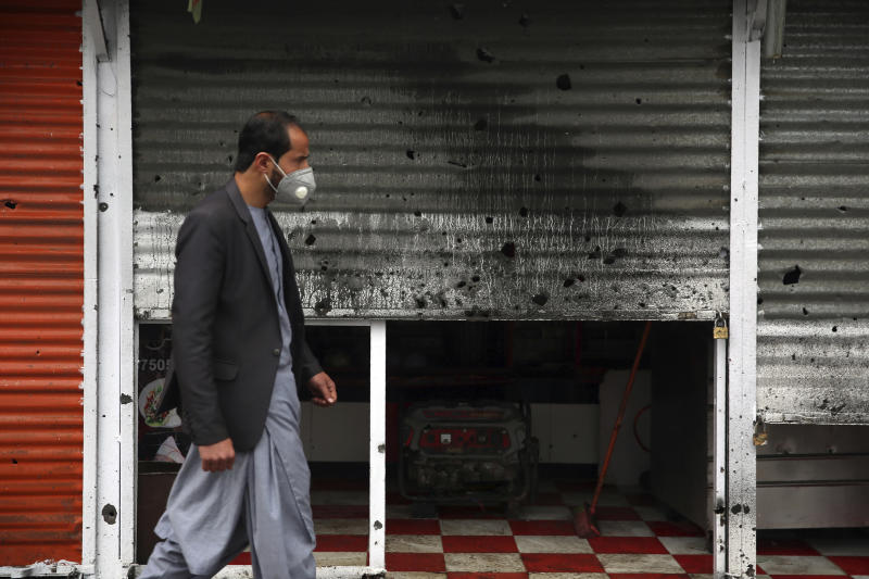 An Afghan man wearing a face mask walks in front of a damaged shop after a bomb explosion in Kabul, Afghanistan, Monday, March 30, 2020. A sticky bomb attached to a vehicle detonated, according to Firdaus Faramraz, spokesman for the Kabul police chief. (AP Photo/Rahmat Gul)