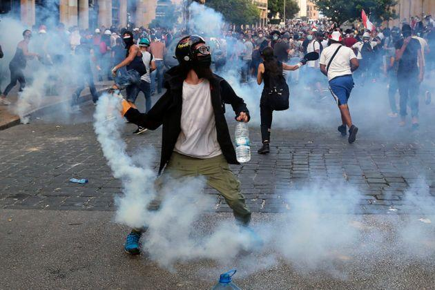 Protesters throw back tear gas canisters towards riot policemen during an anti-government protest.