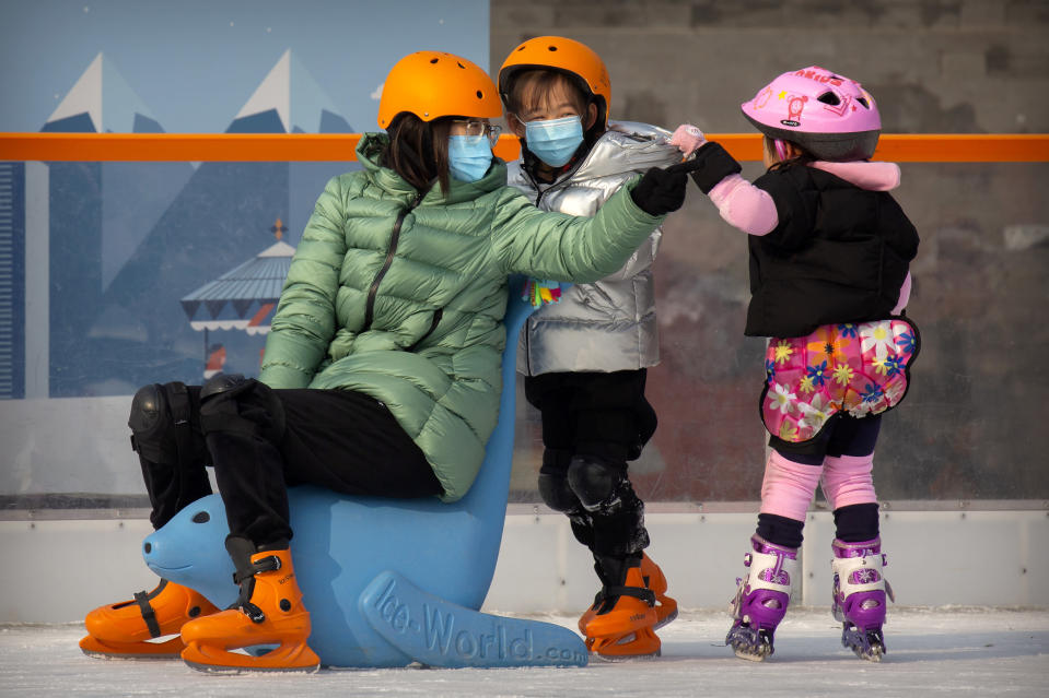 People wearing face masks to prevent the spread of the coronavirus skate at an outdoor ice skating rink in Beijing, Saturday, Jan. 23, 2021. (AP Photo/Mark Schiefelbein)