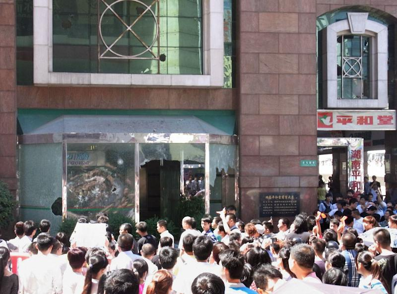 In this Sept. 15, 2012 photo, people crowd outside Japanese supermarket Heiwado after its windows were broken by anti-Japan demonstrators in Shangshain Hunan Province, China. The craggy island specks in the East China Sea aren't even an economic backwater. They have no factories, no highways, no shops, no people — only goats. But the high-pitched row between Beijing and Tokyo over their ownership is exacting a growing toll on Japan, threatening to send its recovery from last year's disasters into reverse. (AP Photo/Kyodo News) JAPAN OUT, MANDATORY CREDIT, NO LICENSING IN CHINA, FRANCE, HONG KONG, JAPAN AND SOUTH KOREA