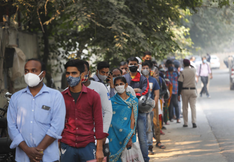 People wait in a queue to get tested for COVID-19 in New Delhi, India, Friday, Nov. 6, 2020. A thick quilt of smog lingered over the Indian capital and its suburbs on Friday, fed by smoke from raging agricultural fires that health experts worry could worsen the city's fight against the coronavirus. Air pollution in parts of New Delhi have climbed to levels around nine times what the World Health Organization considers safe, turning grey winter skies into a putrid yellow and shrouding national monuments. (AP Photo/Manish Swarup)