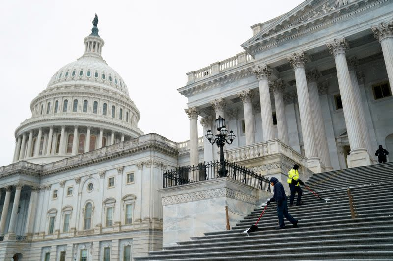 FILE PHOTO: Workers shovel snow from the steps of the U.S. Capitol in Washington