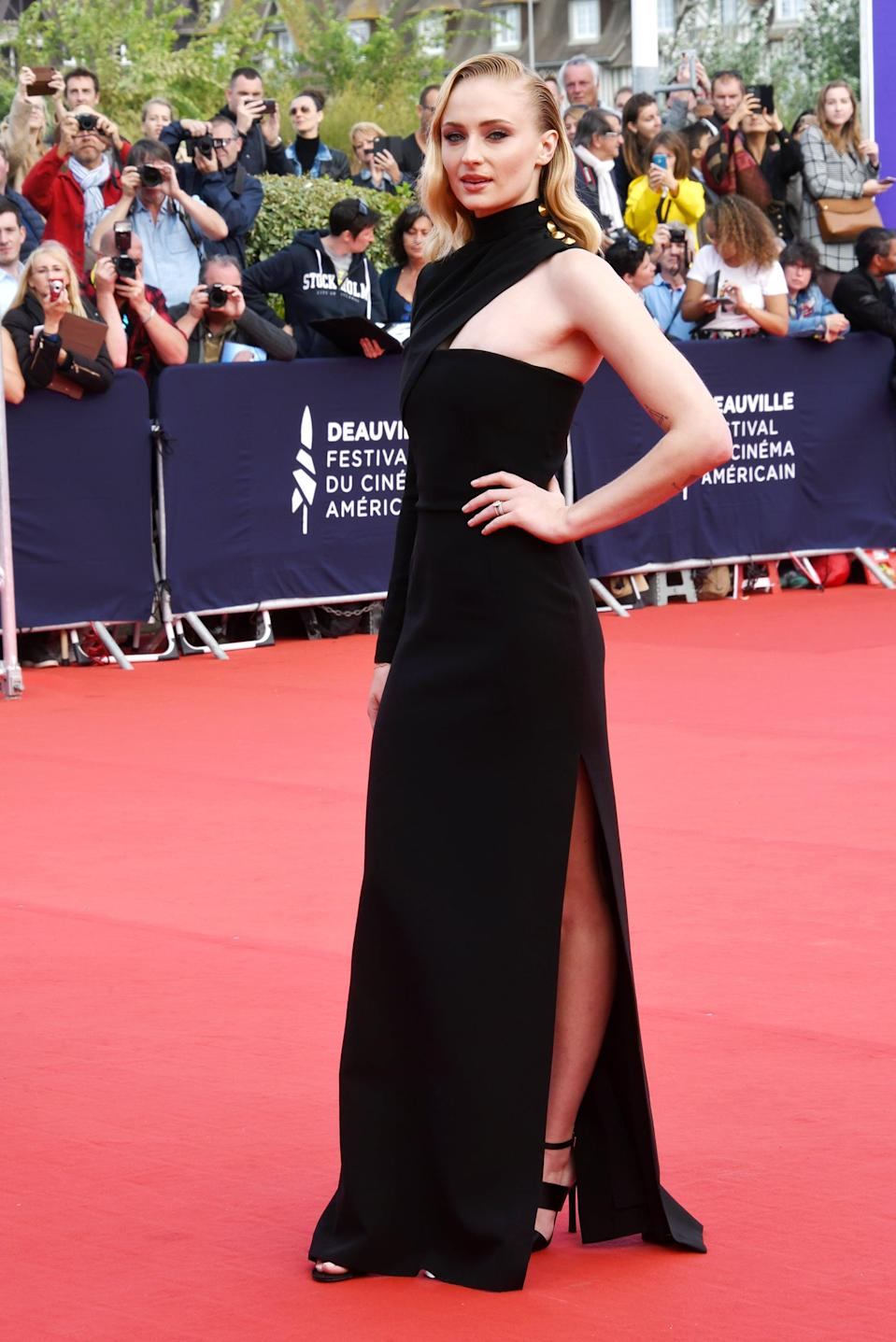 """<p>Sophie attended the 45th Deauville American Film Festival in this sophisticated one-sleeved number with four gold studs at the neckline. She exuded pure glamour with old Hollywood waves and her <a href=""""https://www.popsugar.com/fashion/Sophie-Turner-Engagement-Ring-44145435"""" class=""""link rapid-noclick-resp"""" rel=""""nofollow noopener"""" target=""""_blank"""" data-ylk=""""slk:engagement ring"""">engagement ring</a> stack.</p>"""