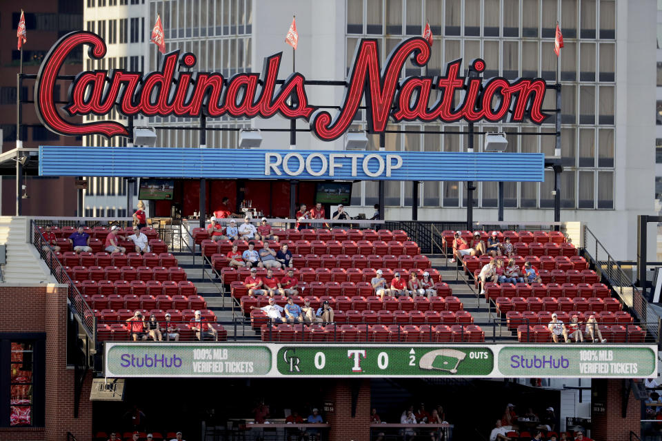 A few fans watch the action from seats across the street outside Busch Stadium as the St. Louis Cardinals and Pittsburgh Pirates play an opening day baseball game without fans in the stadium Friday, July 24, 2020, in St. Louis. (AP Photo/Jeff Roberson)