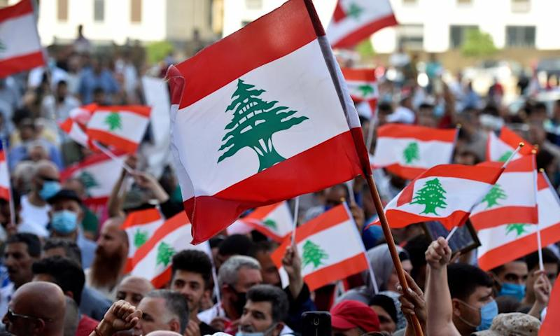 Anti-government protesters wave national flags during a protest in Beirut, demanding a transitional government as Lebanon grapples with its worst economic crisis in decades.
