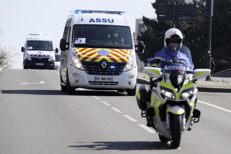 Escorted ambulances drive from the train station to an hospital Wednesday April 1, 2020 in Rennes, western France. France is evacuating 36 patients infected with the coronavirus from the Paris region onboard two medicalized high-speed TGV trains. The patients, all treated in intensive care units (ICU), are being transferred to several hospitals in Britany, as western France is less impacted by the epidemic. The new coronavirus causes mild or moderate symptoms for most people, but for some, especially older adults and people with existing health problems, it can cause more severe illness or death. (AP Photo/David Vincent)