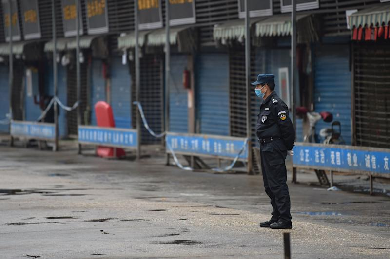 A security guard stands outside the Huanan Seafood Wholesale Market where the coronavirus was detected in Wuhan on January 24, 2020 - The death toll in China's viral outbreak has risen to 25, with the number of confirmed cases also leaping to 830, the national health commission said. (Photo by Hector RETAMAL / AFP) (Photo by HECTOR RETAMAL/AFP via Getty Images)