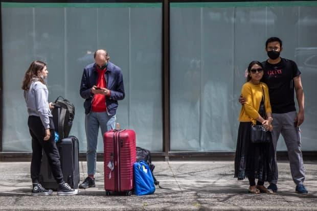 A group of people wait for a bus with luggage in downtown Vancouver, British Columbia on Tuesday, June 22, 2021.  (Ben Nelms/CBC - image credit)