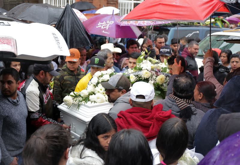 People attend the funeral of several of the victims killed by shooters at a slot-machine arcade in the central Mexican state of Michoacan, in Uruapan