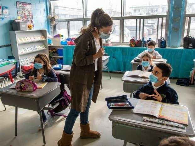 A Montreal teacher and her grade one students wear masks as they attend class. The Calgary Board of Education said Tuesday it will require mandatory vaccination against COVID-19 for employees, volunteers and partners by Dec. 17. (Ryan Remiorz/The Canadian Press - image credit)