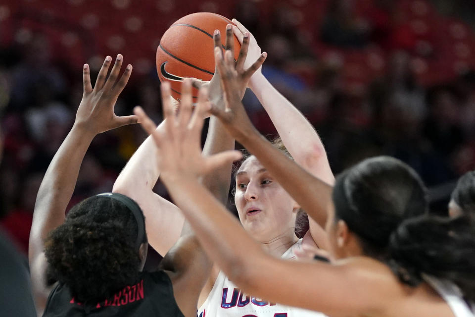 Connecticut's Anna Makurat, center, looks to pass the ball as Houston's Bria Patterson, left, defends during the second half of an NCAA college basketball game Saturday, Feb. 29, 2020, in Houston. Connecticut won 92-40. (AP Photo/David J. Phillip)