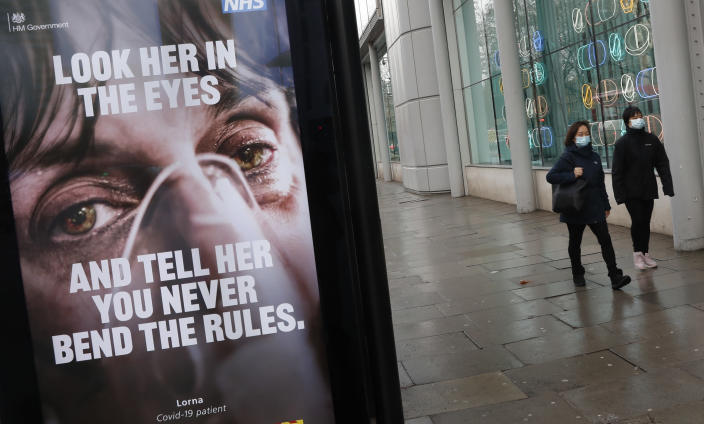 FILE - In this Feb. 2, 2021 file photo, pedestrians wearing masks against coronavirus walk past an NHS advertisement about COVID-19 in London, Tuesday, Feb. 2, 2021. Europe recorded 1 million new COVID-19 cases last week, an increase of 9% from the previous week and ending a six-week decline, WHO said Thursday, March 4, 2021. The so-called UK variant is of greatest concern in the 53 countries monitored by WHO in Europe. (AP Photo/Alastair Grant, File)
