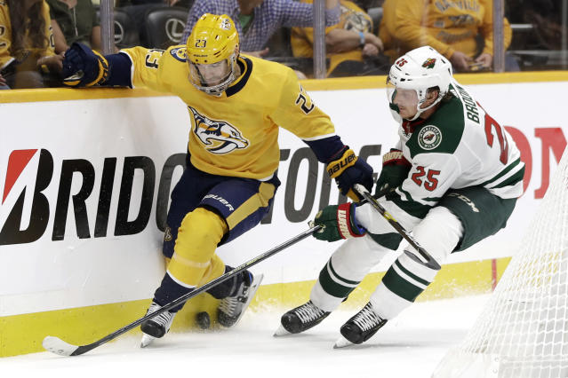 Nashville Predators right wing Rocco Grimaldi (23) works for the puck against Minnesota Wild defenseman Jonas Brodin (25), of Sweden, during the second period of an NHL hockey game Thursday, Oct. 3, 2019, in Nashville, Tenn. (AP Photo/Mark Humphrey)