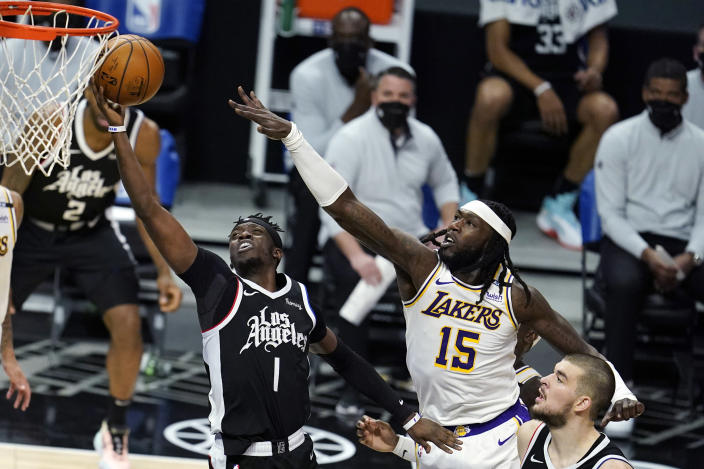 Los Angeles Clippers guard Reggie Jackson (1) drives past Los Angeles Lakers center Montrezl Harrell (15) during the first half of an NBA basketball game Sunday, April 4, 2021, in Los Angeles. (AP Photo/Marcio Jose Sanchez)