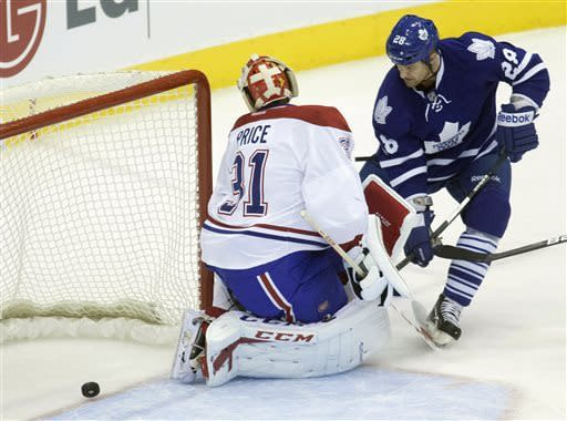 Toronto Maple Leafs' Colton Orr watches the puck shot by teammate Leo Komarov go past Montreal Canadiens goalie Carey Price during the first period of an NHL hockey game in Toronto, Saturday, April 13, 2013. (AP Photo/The Canadian Press, Jesse Johnston)