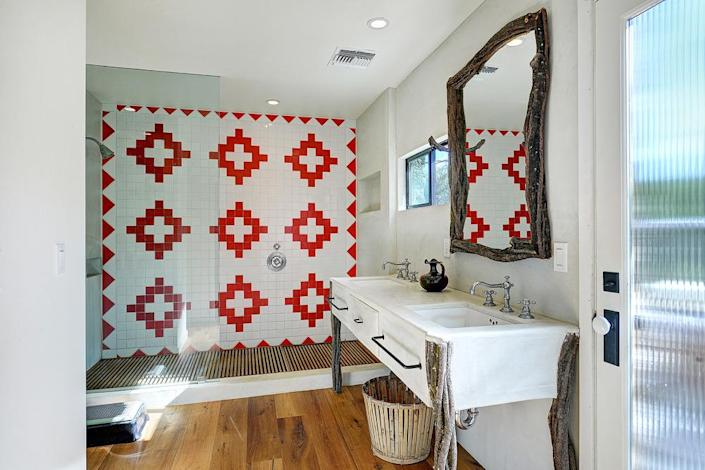 <p>Small design touches, like the tiling on this shower and the bundled wooden legs on the sink, add a rustic touch to the updated main house.</p><p><i>(Photo: Total Agent)</i><br></p>