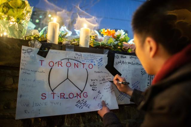 <p>A man writes a message on a sign during a vigil April 24, 2018 in Toronto, Canada, near the site of the previous day's deadly street van attack. (Photo: Geoff Robins/AFP/Getty Images) </p>