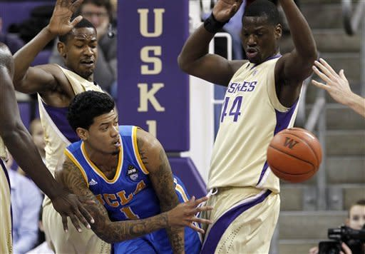 UCLA's Tyler Lamb (1) passes from between Washington's Terrence Ross, left, and Darnell Gant in the first half of an NCAA college basketball game Thursday, Feb. 2, 2012, in Seattle. (AP Photo/Elaine Thompson)