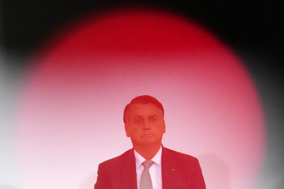 Photographed through the red lightbulb of a videocamera, Brazilian President Jair Bolsonaro attends the launch ceremony for a housing program at Planalto presidential palace in Brasilia, Brazil, Wednesday, Sept. 15, 2021. (AP Photo/Eraldo Peres)