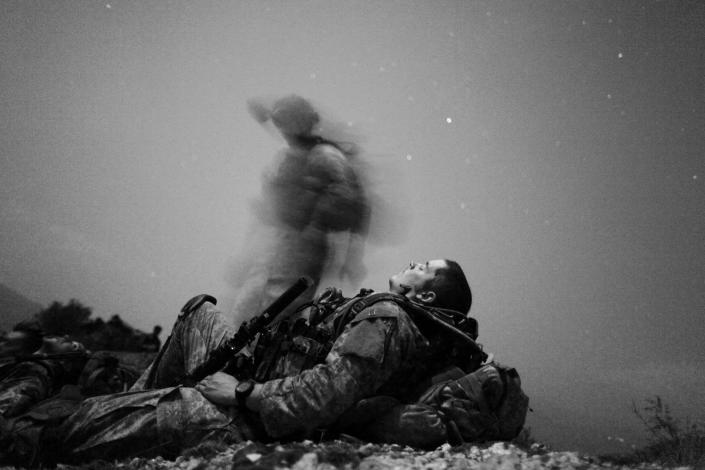 A U.S. soldier of 2-12 Infantry 4BCT-4ID Task Force Mountain Warrior takes a break during a night mission near Honaker Miracle camp at the Pesh valley of Kunar Province, Afghanistan, August 12, 2009. (Carlos Barria/Reuters)